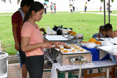 dhamma: Chiang Mai, Thailand -  July 26, 2015: The woman is grilling thailand traditional filled pancake tart for give for free for any people who participating in Dhamma talk fair arranged at Suandok temple.