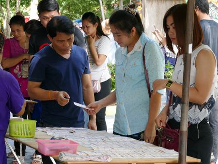loteria: Ang Thong, Tailandia - 1 de agosto de 2015: La gente tailandesa está comprando billetes de lotería en el templo de Muang. Editorial