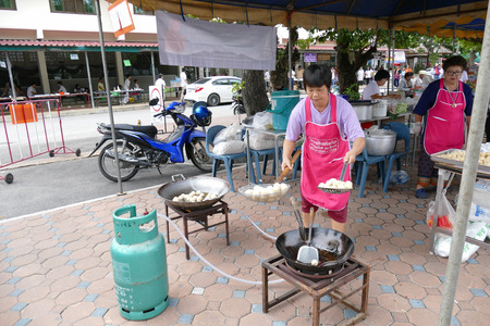 dhamma: Chiang Mai, Thailand -  July 26, 2015: The woman is frying pork ball in the pan for give for free for any people who participating in Dhamma talk fair arranged at Suandok temple.