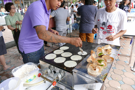 dhamma: Chiang Mai, Thailand -  July 26, 2015: The man is grilling thailand traditional filled pancake tart for give for free for any people who participating in Dhamma talk fair arranged at Suandok temple.