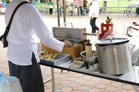 dhamma: Chiang Mai, Thailand -  July 26, 2015: The man is making thailand traditional egg cake for give for free for any people who participating in Dhamma talk fair arranged at Suandok temple.