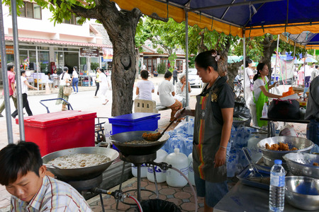 dhamma: Chiang Mai, Thailand -  July 26, 2015: The woman is frying chicken in the pan for give for free for any people who participating in Dhamma talk fair arranged at Suandok temple.