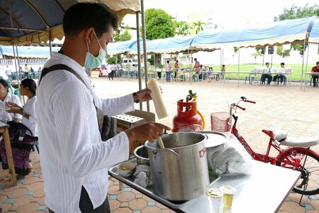 dhamma: Chiang Mai, Thailand -  July 26, 2015: The man is pouring batter for making thailand traditional egg cake for give for free for any people who participating in Dhamma talk fair arranged at Suandok temple. Editorial