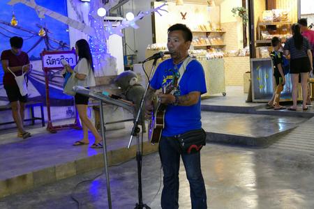 playing the market: Prachuap Khiri Khan, Thailand - July 28, 2015: The man is singing and playing guitar at night market. Editorial