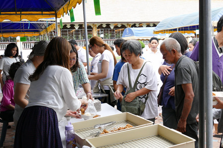 dhamma: Chiang Mai, Thailand -  July 26, 2015: The people is getting fried chicken for free at Dhamma talk fair arranged at Suandok temple.