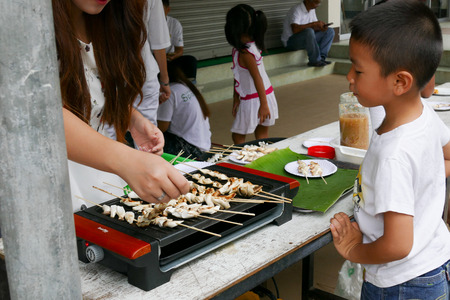 dhamma: Chiang Mai, Thailand -  July 26, 2015: The boy is waiting to get grilled mushroom skewer that give for free for any people who participating in Dhamma talk fair arranged at Suandok temple.