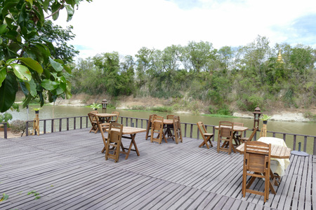 waterside: wooden table and chair on terrace of the restaurant at waterside Stock Photo