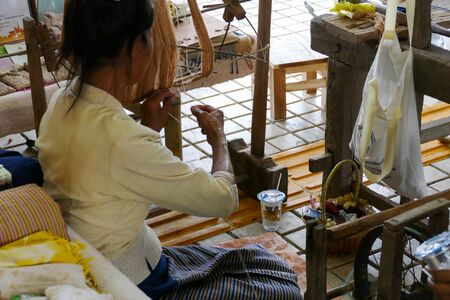 manufacturing materials: Chiang Mai, Thailand - September 8, 2015: woman spinning thailand traditional yarn thread at Lanna expo held at Chiang Mai International Exhibition and Convention Centre.
