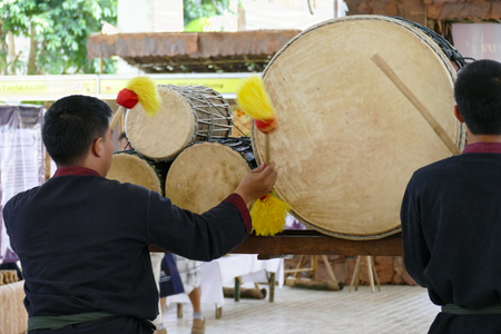 dubbing: Chiang Mai, Thailand - September 8, 2015: the asian man is dubbing retro drum at Lanna expo held at Chiang Mai International Exhibition and Convention Centre. Editorial