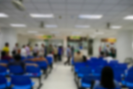 public hospital: blurry defocused image of people standing and sitting in public hospital
