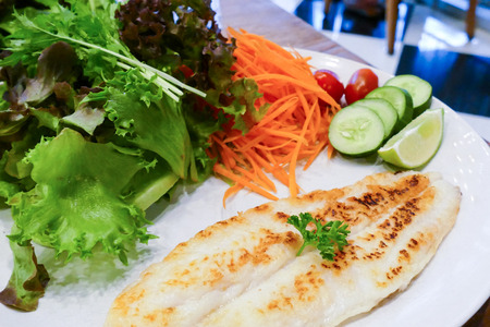cooked fish: grilled fish fillet with sasame sauce and vegetable salad (tomato, carrot, cucumber, lime, red coral, iceberg)