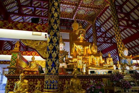 asian angel: golden buddha statue and angel statue in buddhist asian temple building