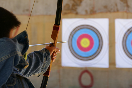 archer is aiming the arrow of the bow at the target