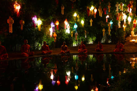 yeepeng: Chiang Mai, Thailand - November 26, 2015: monk meditate beside the pond among the colorful paper lantern in Yeepeng festival at Puntao temple in Chiang Mai, Thailand on November 26, 2015.