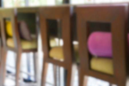 bar stool: blurry defocused image of wooden bar stool beside the window