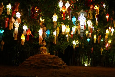 yeepeng: light of colorful paper lantern decorating on the tree and buddha statue at night in Yeepeng festival
