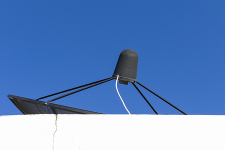 sattelite: black satellite dish on white building with blue sky background
