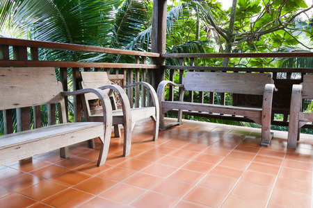 bannister: old wooden chair beside the bannister of the balcony terrace Stock Photo