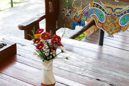 ramo de flores: ramo de flores de colores en el florero sobre la mesa de madera