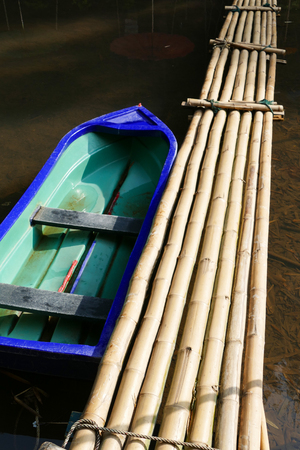 across: blue boat and bamboo footbridge across the creek