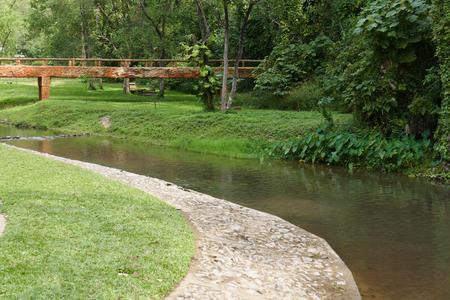 across: footbridge across creek stream and walkway in the park