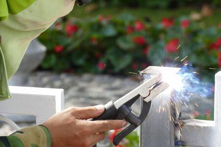 llamas de fuego: The worker welding the iron steel pole Foto de archivo