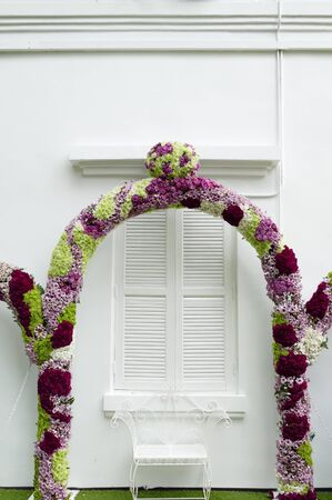 flower arrangements: arch decorating with blooming flower in front of white wooden door