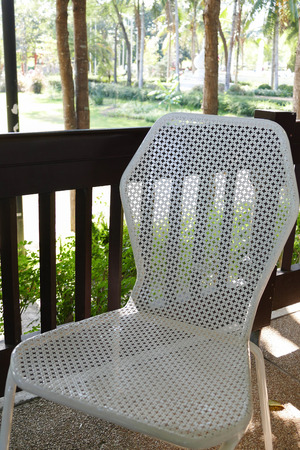 chair garden: white metal chair on the balcony beside the garden