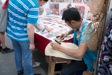 shadow puppet: Chiang Mai, Thailand - January 31, 2015: Artist making thailand traditional shadow puppet at Sunday walking street at Tha Phae Gate in Chiang Mai, Thailand on January 31, 2015. Editorial