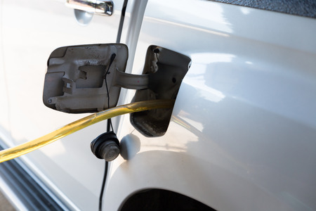 fill up: people using traditional way to fill up the gas tank with rubber tube Stock Photo