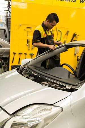 glazier: Chiang Mai, Thailand - February 16, 2016: Repairman is repairing windshield of the car at good sure glass company in Chiang Mai, Thailand on February 16, 2016.