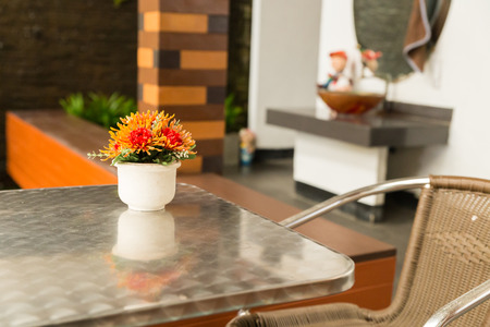 patio chairs: bouquet of artificial orange flower on metal table with wicker chair on patio Stock Photo