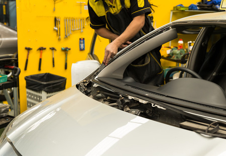 coachwork: Repairman in workwear is repairing windshield of the car Stock Photo