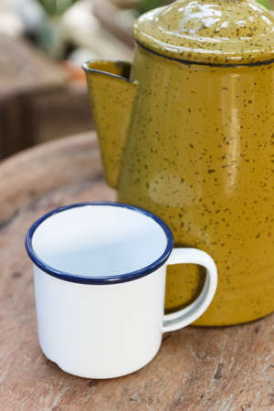tiffin: white cup and old yellow jug and tiffin on wooden desk Stock Photo