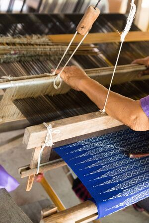 loom: Woman using traditional loom to weave thailand textile