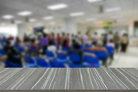 public hospital: empty wooden table with people standing and sitting in public hospital blur background for displaying your product Stock Photo