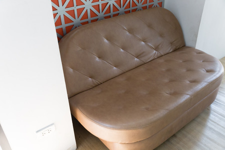 living room wall: brown leather sofa beside orange wall in living room Stock Photo