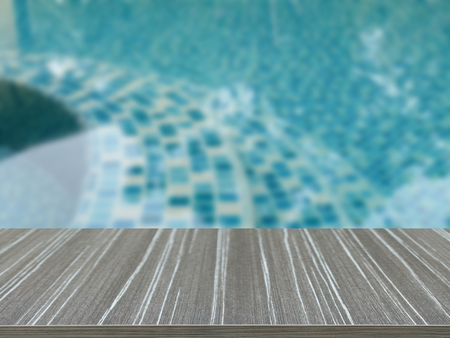 table surface: empty wooden table with water surface of the swimming pool blur background for displaying your product