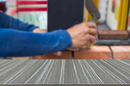 redbrick: the worker is using the trowel for masoning the brick (blur background and wooden table for displaying your product)
