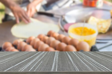 cook griddle: egg and butter for making an indian traditional crispy flat bread or roti on the griddle (blur background and wooden table for displaying your product)