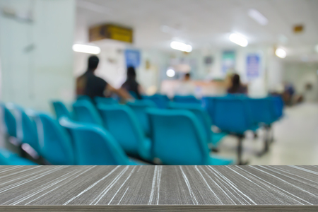 public hospital: patient sitting on chair waiting for doctor in public hospital (blur background and wooden table for displaying your product)