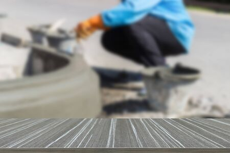 table surface: worker apply cement over the surface of footpath edge (blur background and wooden table for displaying your product)