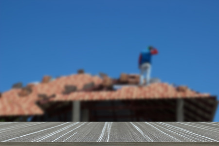rafter: man work on tile arrangement on home roof construction (blur background and wooden table for displaying your product)