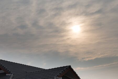 sun roof: view of home roof, sun and cloud at dusk in the evening Stock Photo