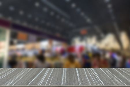 tradeshow: people shopping in fair tradeshow which retailer selling various product (blur background and wooden table for displaying your product) Stock Photo