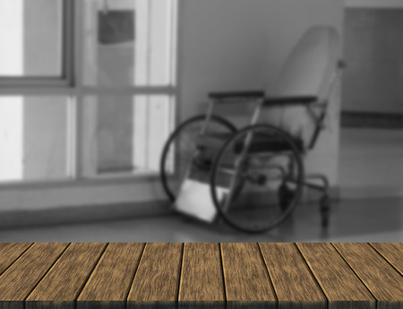 paraplegico: empty wheelchair in hospital corridor (blur background with wood table top for display or montage your product)