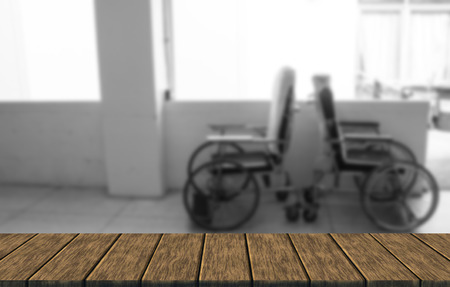 paraplegico: silla de ruedas vacía en el pasillo del hospital (desenfoque de fondo con mesa de madera para la visualización de montaje o su producto) Foto de archivo