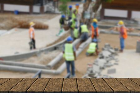 constructing: workers are constructing pathway at the construction site (blur background with wood table top for display or montage your product)