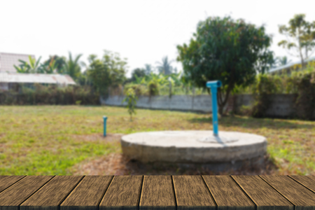 septic: underground cement cylinder of lavatory cesspit in lawn yard (blur background with wood table top for display or montage your product)