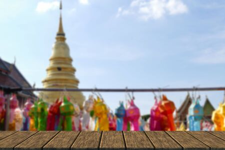 yeepeng: colorful paper lantern decoration for Yeepeng festival and golden pagoda monument at temple in Thailand (blur background with wood table top for display or montage your product)